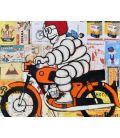 Bibendum Michelin avec un casque rouge et sur une moto orange