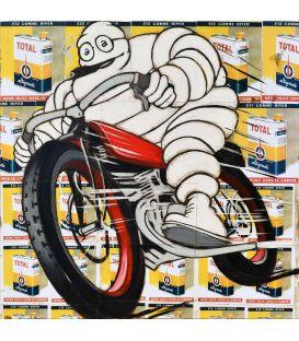 Michelin sur une vieille moto rouge sur un fond de vieilles publicités pour l'huile Total
